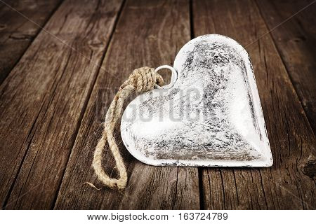 Single rustic metal heart ornament on a vintage wooden background