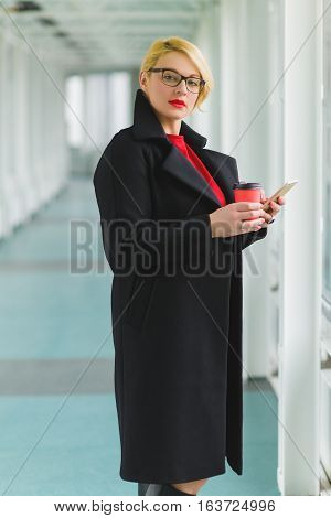 fashion woman using smart phone and holding take away coffee in hall.