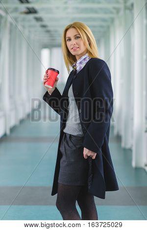 fashion elegant woman dressed coat stand in lobby.