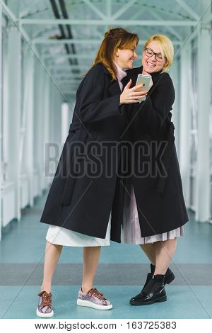 Two smiling elegant woman dressed in coat looking at smart phone.