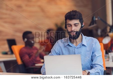 Businessman Wearing Headphones Working On Laptop In Office.