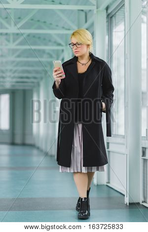 fashion elegant woman dressed coat going in lobby.