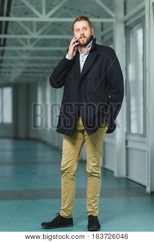 young successful businessman with cell phone dressed coat