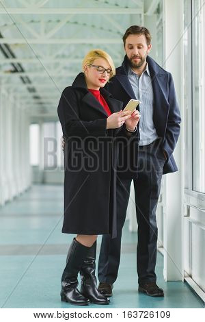 Elegant couple dressed in coat looking on smart phone at lobby.