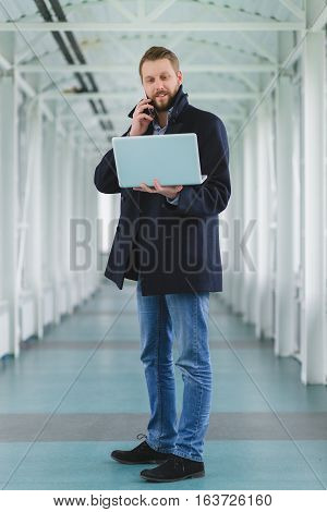 young businessman with laptop in lobby or hall.