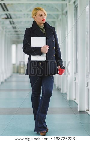 Portrait of blond businesswoman holding coffee and laptop in lobby.