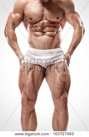 Strong Athletic Man Shows Legs And Abdominal Muscles
