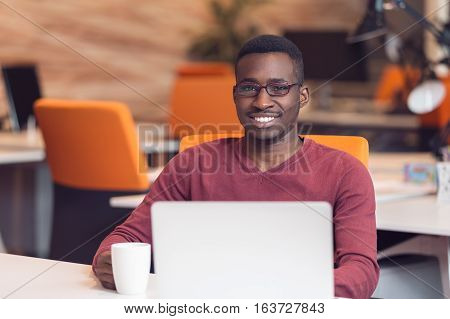 Handsome smiling successful African American man wearing formal suit, oval glasses, using laptop computer for distant work