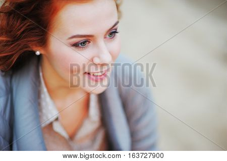 Portrait of charming smiling girl with bright red brown hair on blurred background side view closeup.