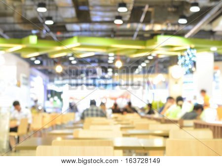 Atmosphere of food center within modern shopping mall blur background.