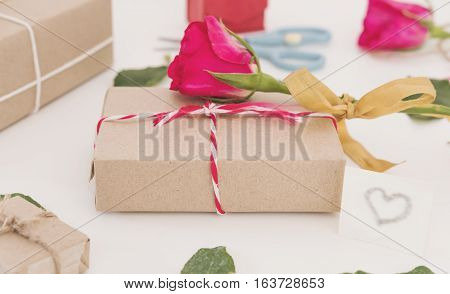 Valentines gift preparation, parcel gift box with roses and leaves, on white table