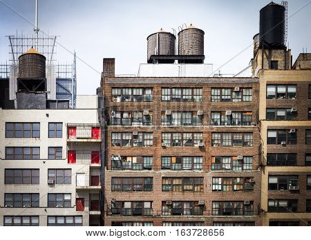 Old vintage apartment buildings with wall of windows and water towers on the roof tops in downtown New York City