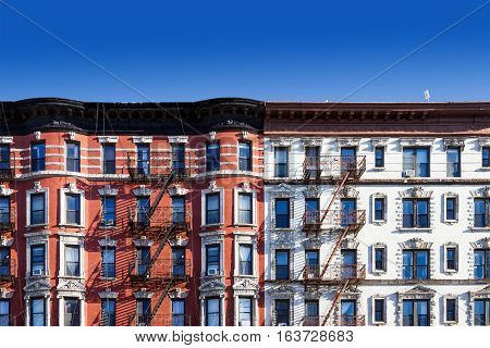 New York City block of old historic apartment buildings in the East Village of Manhattan NYC with a clear blue sky background