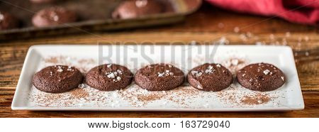 White plate of dark chocolate cookies on a wooden table