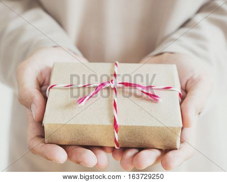 A man holding parcel post gift box on hand