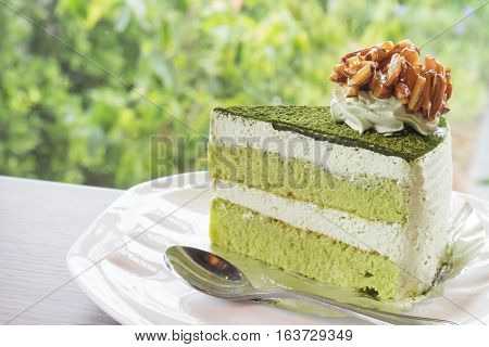Closeup matcha green tea cake in coffee shop with nature background