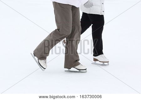 foot skating of two girls on the ice rink