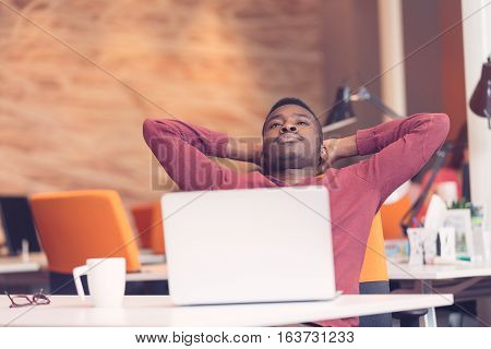 Young African-American business man taking a break at his desk.
