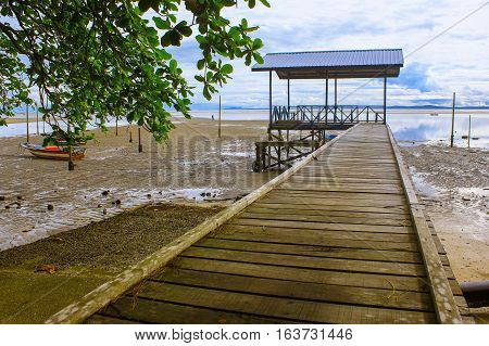 Morning view of the fishing jetty at Tanjung Aru village,Labuan,fishing village with blue sky and clouds at low tide