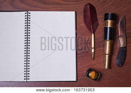 a sheet of paper from a notebook a hunting knife fountain pen and ink spyglass on wooden background copyspace