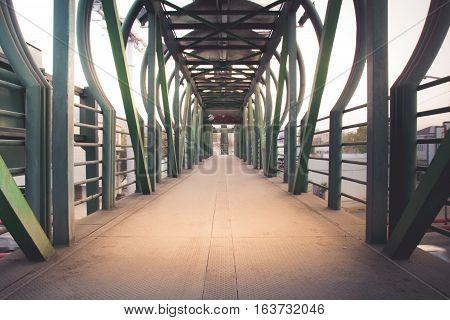 Photograph of a metal pedestrian bridge on an urban scenario