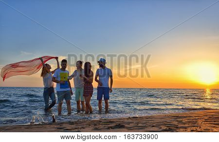 group of happy young people dancing at the beach on beautiful summer sunset.