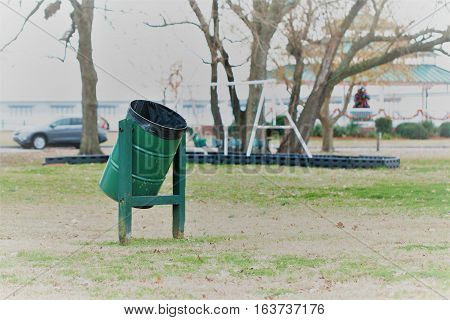 Green metal garbage can in a park setting