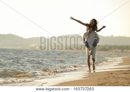 A guy carrying a girl on his back, at the beach, outdoors.