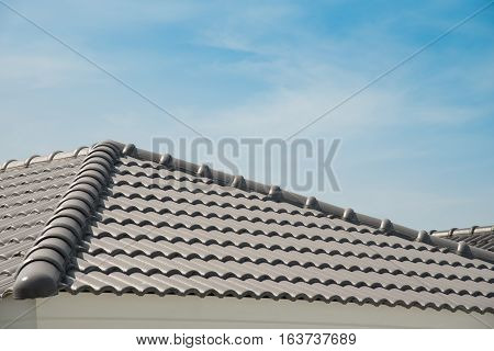 Rows of roof tiles on the top of house with sky background.