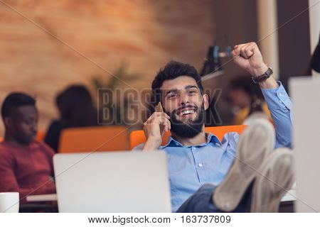 Relaxed young businessman at workplace at early morning, relaxing, at modern startup office.