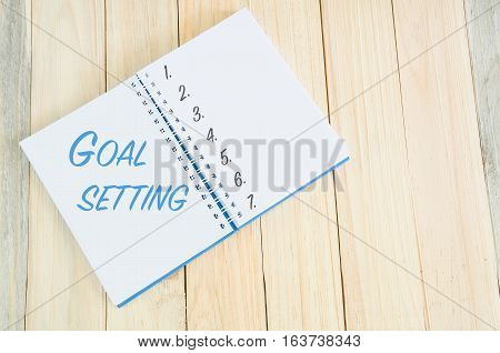 ( Setting Up Goal business conceptual. ) Goal setting as memo on notebook with wooden background