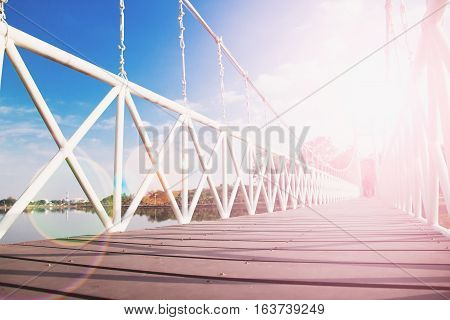 Rope bridge with sunset reflection and blue sky