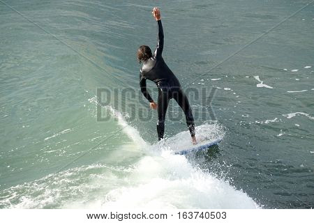 A man trying to balance while surfing