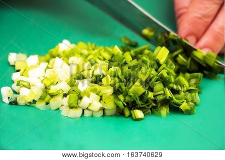 Woman chopping green onion with knife on the table in the kitchen. Healthy eating, cooking, vegetarian food.