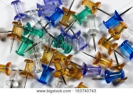 A macro shot of various colored pushpins.