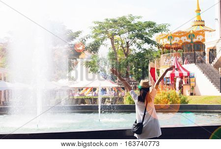 Young woman in happiness feeling with amusement park ride background