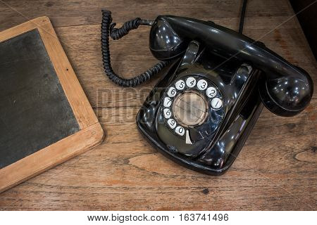 Black Antique Vintage Analog Telephone Dialing Or Scrolling Phone On Old Wall With Old Slate. Contac