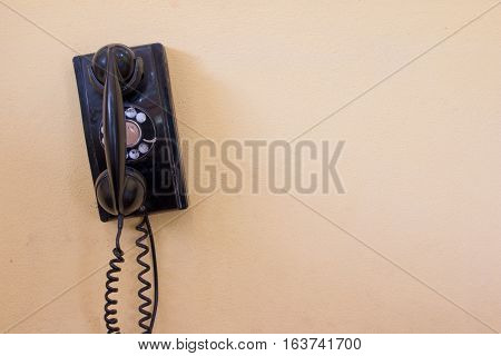 Black Antique Vintage Analog Telephone Dialing Or Scrolling Phone On Old Wall. Contact Us Concept.