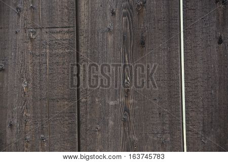 Close up of wide planks that make up a wooden fence
