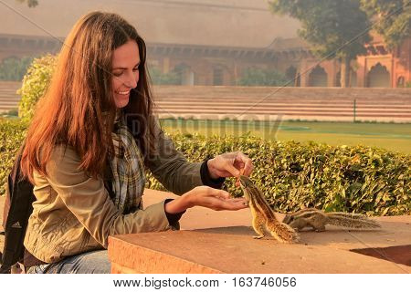 Young woman feeding Indian palm squirrels at Agra Fort Uttar Pradesh India. This fort is a very popular tourist site in Agra