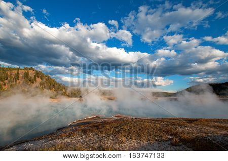 Cloudscape above steam at Excelsior Geyser in the Midway Geyser Basin next to the Firehole River in Yellowstone National Park in Wyoming USA