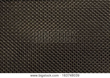 Golden fishnet cloth material as a texture background. Nylon texture pattern or nylon background for design with copy space for text or image.