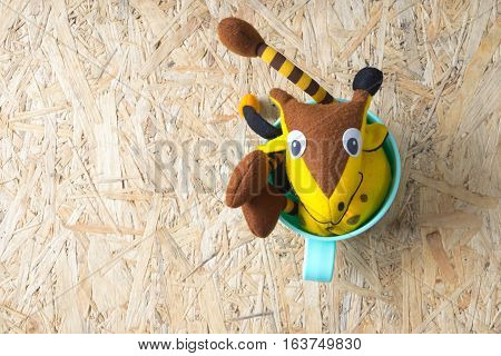 Cute Giraffee soft toy in green plastic on wood background toys for newborn baby