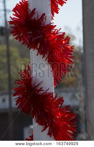Red Christmas garland wrapped around a white pole