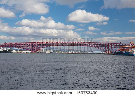 Minato Bridge in Osaka, Japan over seaport skyline and blue sky