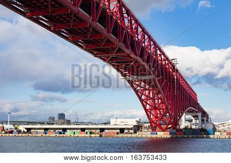 Minato Bridge In Osaka, Japan Over Seaport Skyline And Blue Sky Background