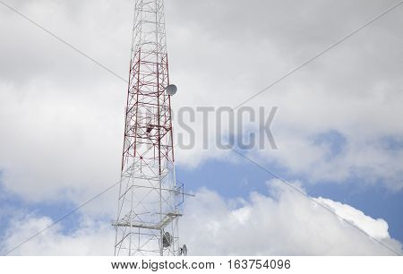 Communications satellite tower in the cloudy sky
