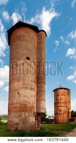 Tall red barn in italian farm with blue sky
