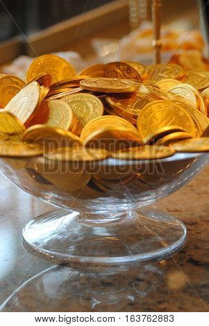 Glass bowl with chocolate shiny gold medals