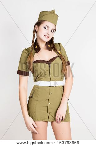 sexy fashionable woman in military uniform and forage-cap, posing.